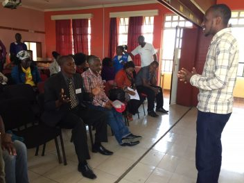 Mukuru resident and workshop facilitator Kelvin encourages policy-makers to take part in the performance. Photo: Fiona Lambe / SEI.
